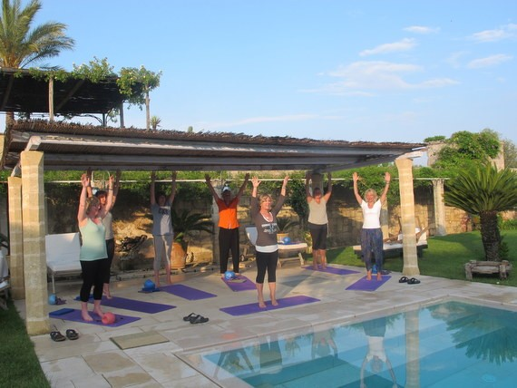 Pilates group with hands up high by the pool in Puglia