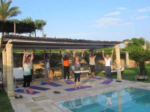 Women doing Pilates besides pool on a sunny day