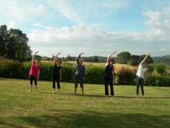 5 women doing Pilates in the Tuscan sun