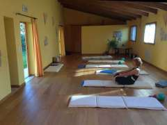 Pilates guest warming up in studio surrounded by mats