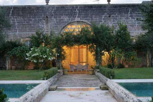 Puglia villa from outside in idyllic garden.
