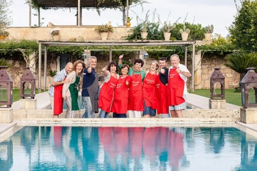 Nine cooking holiday guests laughing in front of swimming pool in our villa in Puglia.