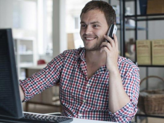 Young man in office smiling and talking on the phone