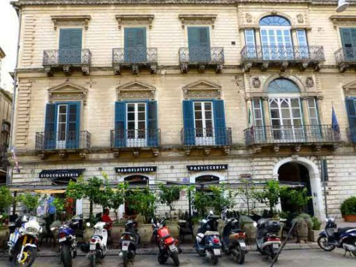 Vespas in front of Sicilian building.
