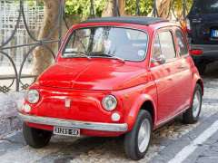 Small and bright red car parked in Sicilian streets