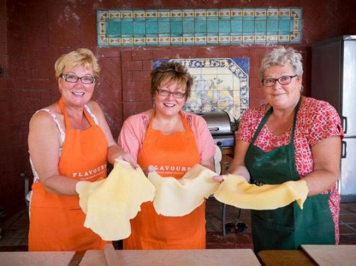 Three ladies in aprons smiling and holding pizza dough